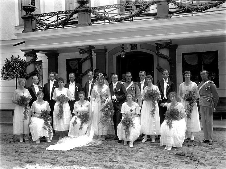 Brudparet med tärnor och marskalkar har fotograferats framför entrén till Bergkvara slott.
