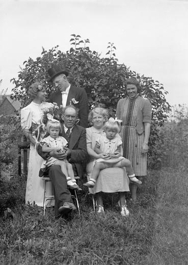 Foto av ett brudpar med familj, fotograferade i en trädgård.