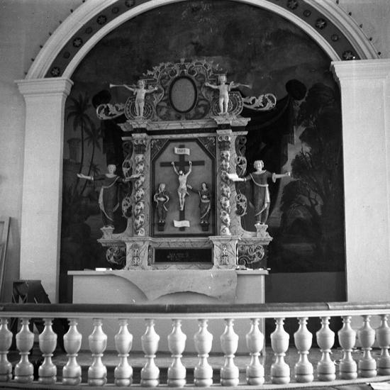 Foto av altaruppsats, uppsatt på prov vid restaurering.Slätthögs kyrka. Tidigare fanns här en medeltida stenkyrka. Den ersattes 1841–1842 av en nyklassicistisk kyrka efter ritningar av Samuel Enander. Invigningen kom att dröja till 1855 och förrättades av biskop Christopher Isac Heurlin. Kyrkan som är uppförd i sten , vitkalkad och spritputsad består av ett rektangulärt långhus med avrundade hörn i kordelen. Kyrkorummet är av salkyrkotyp med tunnvalvstak.  I koret fanns ursprungligen en altarpredikstol. Korväggen och kortaket var dekorerat med målningar. Vid 1955 års renovering som utfördes efter förslag av arkitekt B. J. Jörgensen avlägsnades målningarna bortsett från dekoren i kortaket som behölls. Altarpredikstolen flyttades från koret till kyrkorummets norra vägg. I dess ställe uppsattes den gamla kyrkans altaruppsats från 1742.