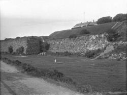 Vy över en stor gräsmatta invid de höga fästningsmurarna til