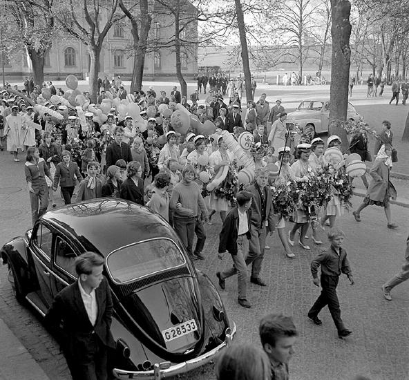 Studenterna, tredje d. 1960. Studenterna m.fl. tågar längs Skolgatan, mot Linnéparken och talet vid Esaias Tegnérs staty. I bakgrunden syns Norrtullskolan.