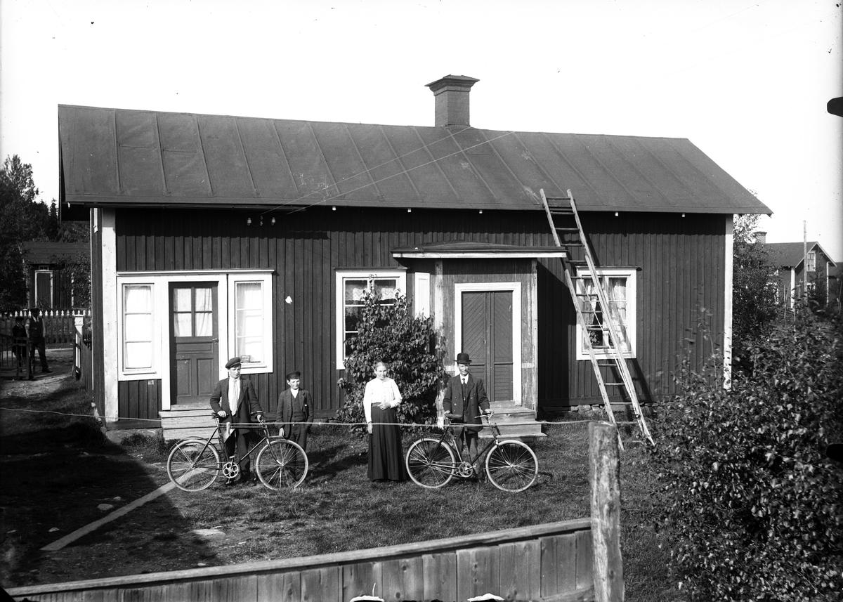 Familj framför bostadshus, okänd plats.