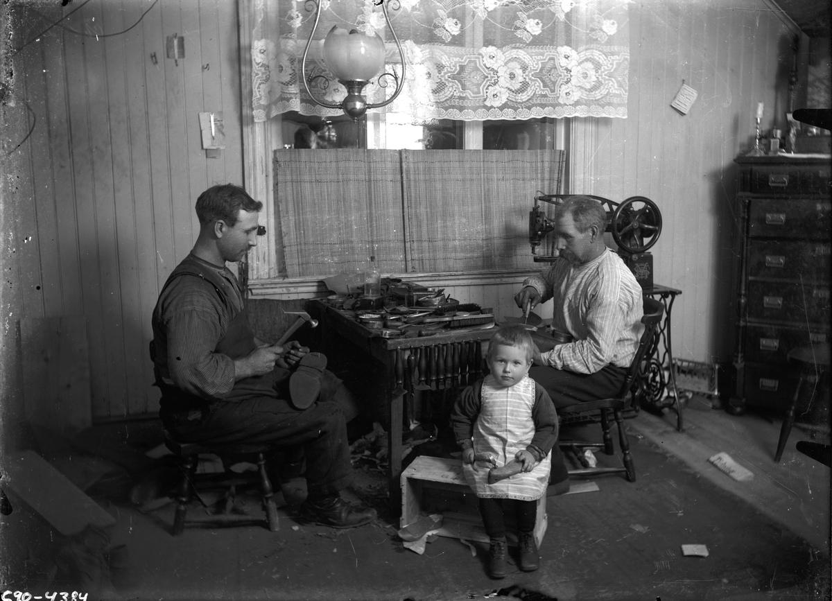 Två män och ett barn i skomakeri.
