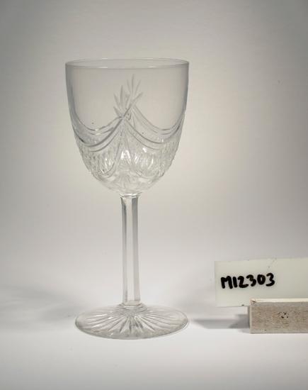 """Glas. Servis """"Alida"""". (K 70). Facettben. Ofärgat klarglas. Ovan angivna diameter avser fotdiameter. Inskrivet i huvudkatalogen 1942.  Kataloger: Se 1904 års katalog. Funktion: Vinglas"""