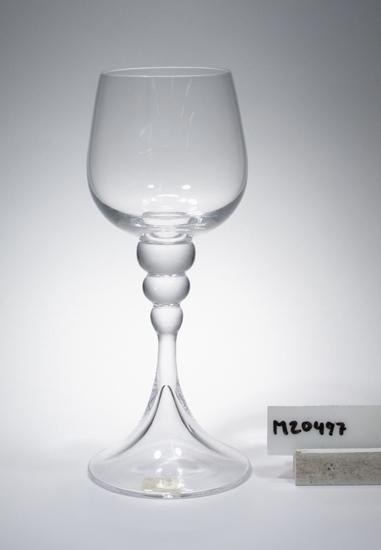 """Vinglas.  Formgivet av Bengt Orup. Färg: Ofärgat klarglas. Mått: Ovan angiven diameter avser övre diameter. Märkning: Självhäftande lapp. Se """"Signering, märkning"""" ovan. Inskrivet i huvudkatalogen 1968.  Del av servisen presenterad på """"Reflection in Glas"""", juni 1969.  Bengt Orup (1916-1997), konstnär, glasdesigner m.m. Funktion: Vinglas"""