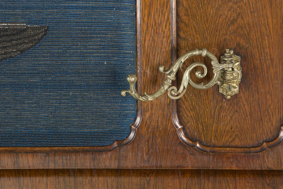 Dekor på frontlokk laget av perler som forestiller et englehode med vinger.