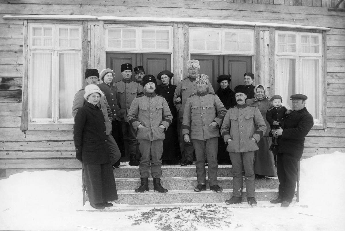 På trappan till mangårdsbyggnaden i Skinnars. Från vänster: Skinnar-Brita (Persson), okänd, Edla Olsson, tre okända militärer, Målar-Ebba (?) (Wikström), den barhuvade till höger är Skinnar-Pelles syster Ella (Hansson), damen i huckle längst till höger är Skinnar-Marta. Längst fram till höger är Skinnar-Pelle med Jonas i famnen. Foto 1914 eller 1915.