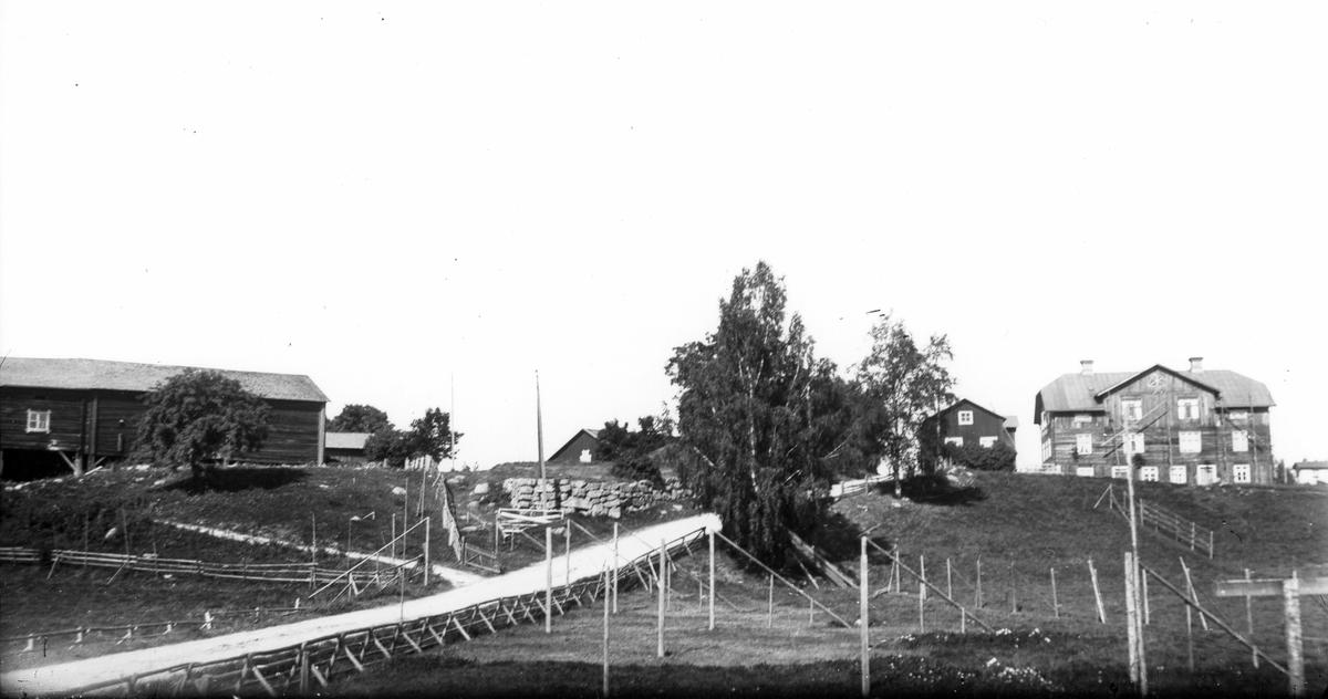 Till vänster Nils-Nils, till höger Skinnars, i mitten gamla landsvägen. Troligen 1913.