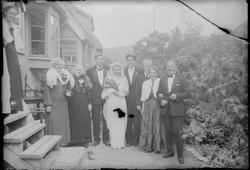Brudepar med gjester utenfor hus.