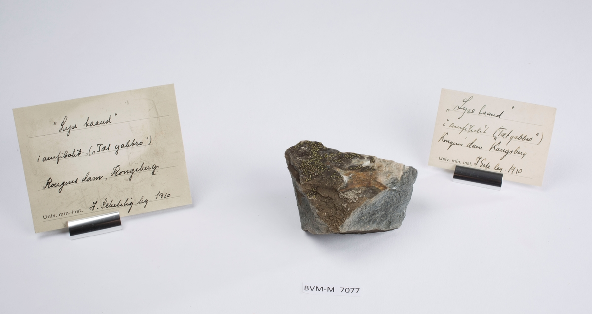 To etiketter i eske:  Etikett 1: «Lyse baand» i amfibolit («Tæt gabbro») Kongens dam, Kongsberg J. Schetelig leg. 1910.  Etikett 2: «Lyse baand» i amfibolit («Tæt gabbro») Kongens dam, Kongsberg J. Sch leg. 1910.