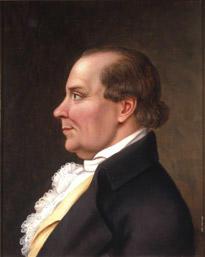 Portrett av Peder J. Cloumann. Profil. Mørk drakt, hvit skjorte med kalvekryss, lys gul vest. (Foto/Photo)