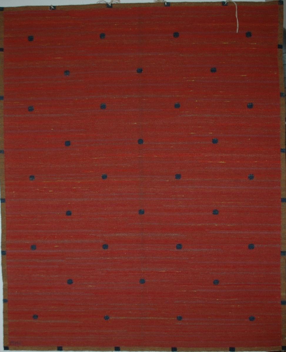 Röd duk, Rölakan, 154 x 129, före 1919. Varp vitt lingarn. Botten i rött ullgarn, insprängt med rödviolett, gulbrunt och grått. De ytterst sparsamma mönsterformerna, blå moucher, i blått. Sign. M.M.F. Äldre katalogisering av Elisabeth Thorman (enl. uppgift).  Längd: 154 cm          Bredd: 129 cm Varp: 4 tr/cm            Inslag: ca 9/cm Varp vitt ullgarn, inslag brunt, 2 nyanser gulbrunt, blått, mörkblått, ljusbrunt, rödgult, gulrött, brunrött, rödblått, grått och gult ullgarn troligen 1 tr, röllakan. Mittpartiet små runda former i mörkblått jämnt fördelade över väven mot en botten i flera nyanser rött och inplockade trådar i gult fördelade över väven, runt omkring en smal fyrkantig bård i gulbrunt med små kvadrater i mörkblått jämnt fördelade över bården. Väven avslutas med s.k. falsk stadkant.  Vid ena hörnet invävd signatur MMF i blått ullgarn.  Ett ca 10 cm brett vitt tygstycke i bomull, tuskaft, fastsydd på avigsidan längs ena kortsidan.  4 st snören fastknutna längs ena kortsidan.  Komponerad av Märta Måås-Fjetterström.  Ulla-Britta Sandström april 1980  Se bilaga  Foto Nordiska museet: 388 Q.l. (se katalogkort).