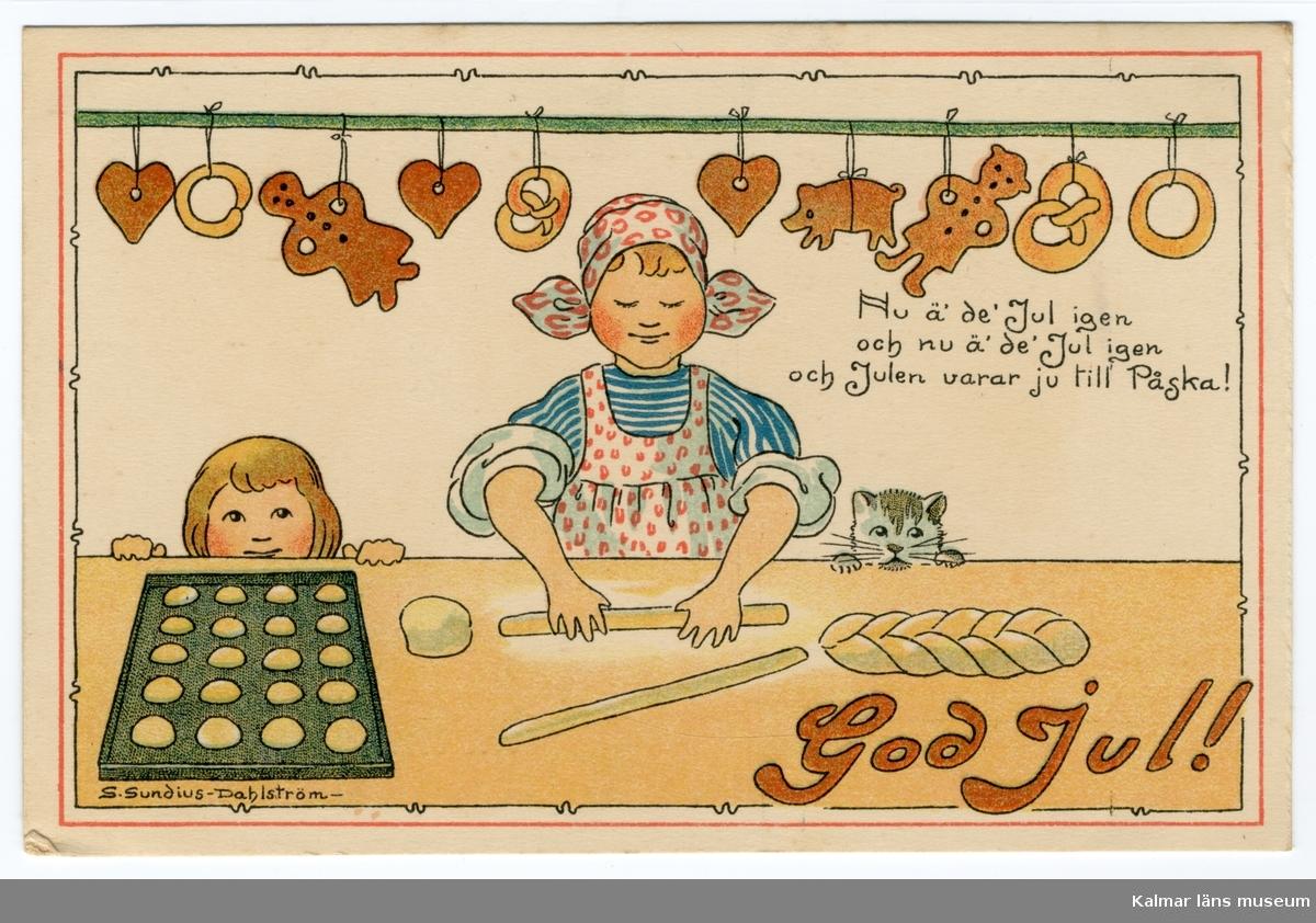 En kvinna står vid ett bord eller en bänk och bakar, hon rullar en deg till en längd. Bredvid henne till höger tittar en katt upp och till vänster tittar ett barn upp över bordskanten. På bordet ligger en plåt med bullar, deg och en vetelängd. Ovanför henne hänger pepparkakor och kringlor fastknutna på en stång.