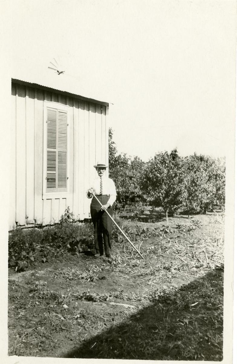 Bildet viser en mann som står utenfor et hus med ei rive i hånda
