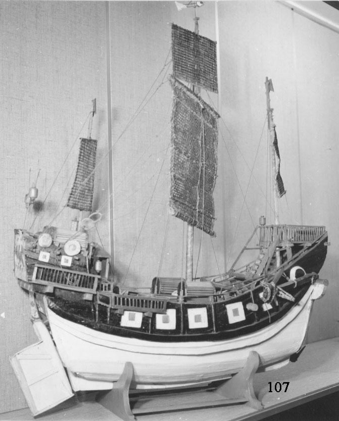 Fartygsmodell Kinesisk Djonk av större sorten, tacklad och inredd, försedd med 3 master med rår samt segel av bast. På däck finns tre stycken och på akterbyggnaden tre stycken hytter av bambu. Modellen av trä är svartmålad. På sidorna finns vita fyrkanter med rött inre fält. Undre delen av modellen är vitmålad. I aktern synes målningar föreställande fågel Fenix samt en europeisk man köpande varor av en kines. I bakgrunden finns även en drake. I förstäven är om styrbord och barbord målat ett öga, som enl. kinesisk tro styr båten undan faror.
