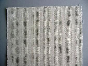 Ingeborg Burin, Venjan, vävde 1971 - 35,7m á 7:-. Gardinen är vävd i myggtjällsrutor med tuskaft emellan. Varp i Cottolin 28/2 och inslag av towgarn 12. Gardinen är ljust grå. Dubblett finns.