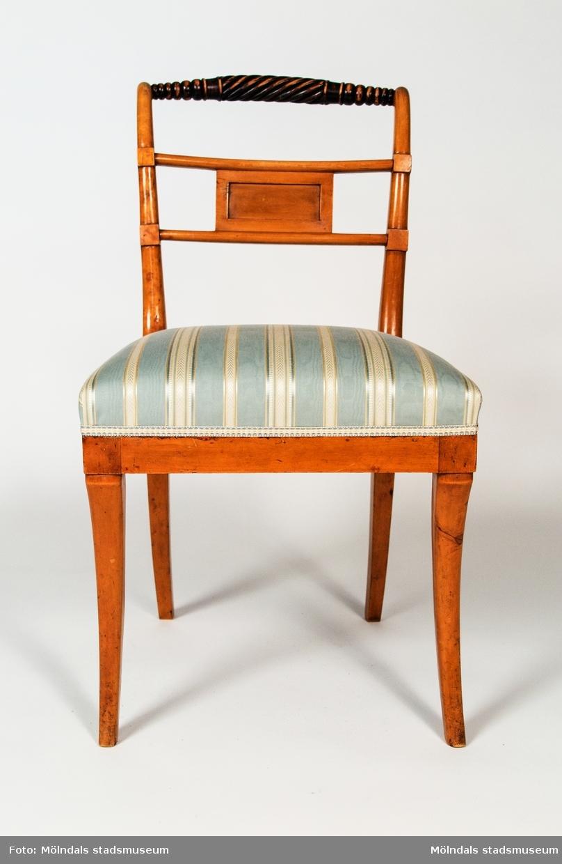 """Stol av polerad björk med svärtade partier. Tillverkad i Lindome omkring 1820. Svarvad överliggare med en sprialvridet mittparti, som påminner om en repstump. Liten rektangulär ryggbricka inplacerad mellan två horisontella spjälor. Sabelformade framben. Fast stoppad sits klädd med blå- och beigerandigt tyg.Brännstämplad i baksargen """"AES:H."""" - Andreas Ericsson, Hassungared 1 (1790-1871).Stoltypen är vanlig i lindomeproduktionen omkring 1820 och kallas vanligen för """"Trafalgarmodell"""" då den återgår på en engelsk stol som tillverkades för lord Nelson mäss på skeppet Victory.Stolen är i par med MM02393"""