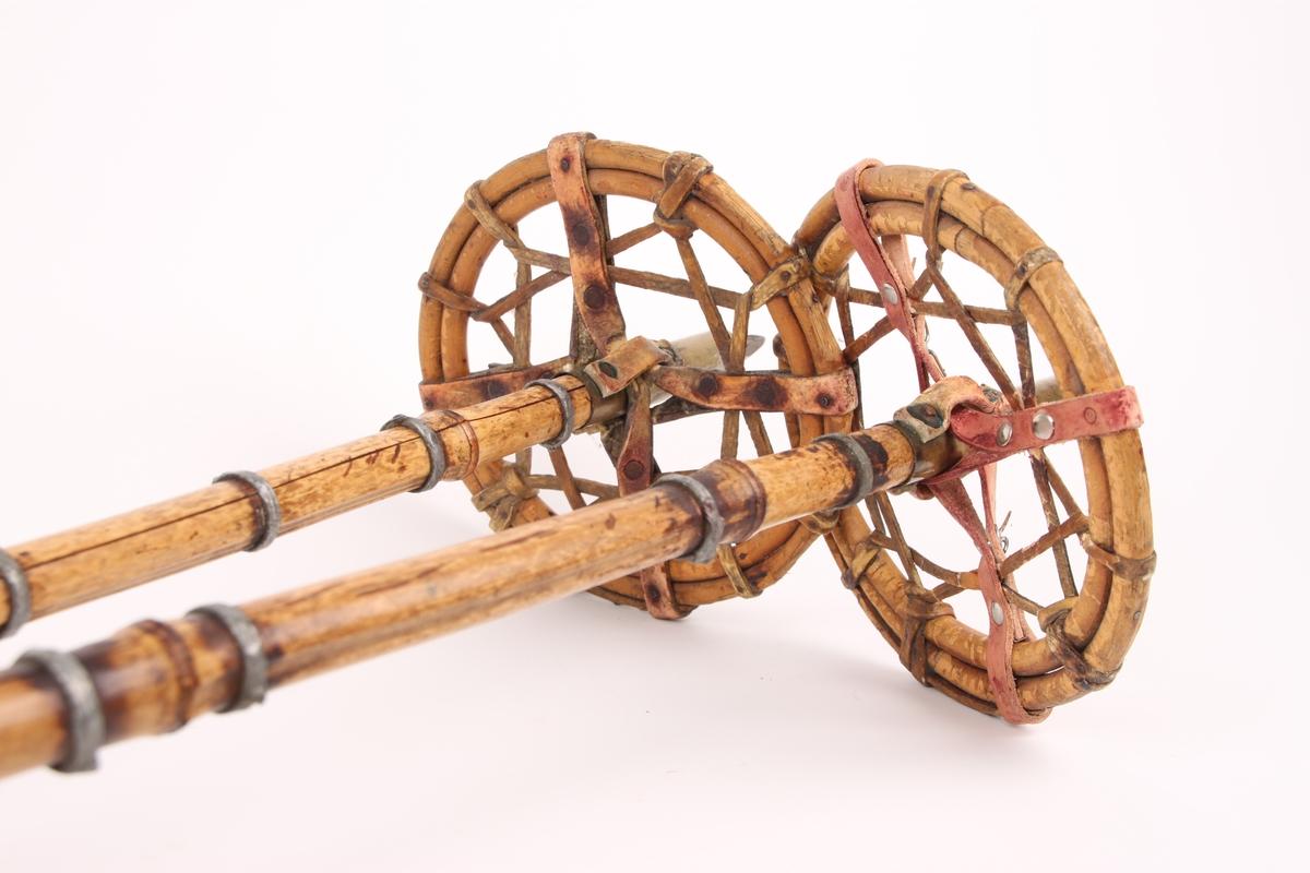 Et par bambusstaver med monogram brent inn øverst ved håndtaksremmen i lær. Staven er forsterket med ringer av blylegering. Flettverk-trinser bestående av røde skinnremmer og fettlærsremmer er festet til en dobbel trinsering av spanskrør.