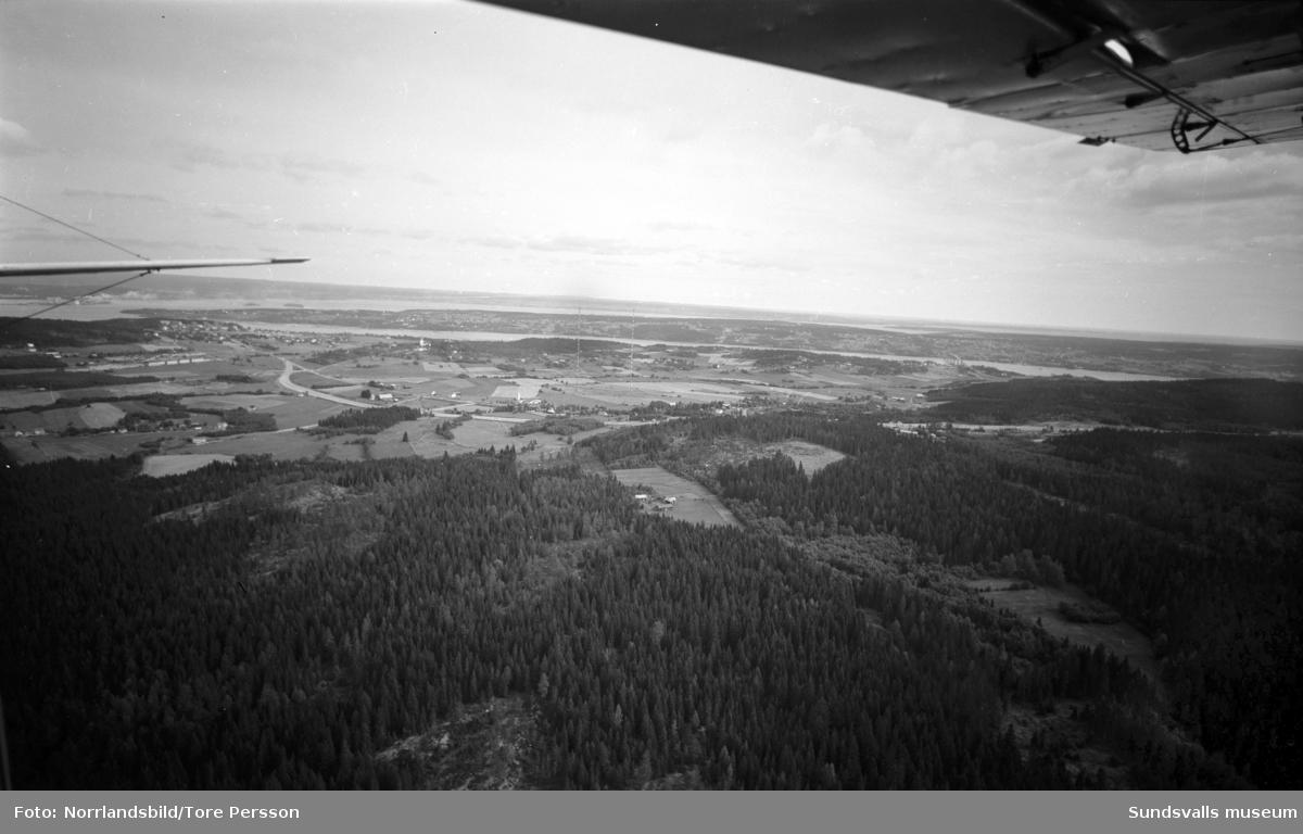 Flygfoto över Birsta och Ljustadalen tagen mot nordost. Mitt i bild syns de numera rivna radiomasterna, till vänster Sköns kyrka, till höger den nybyggda Alnöbron.