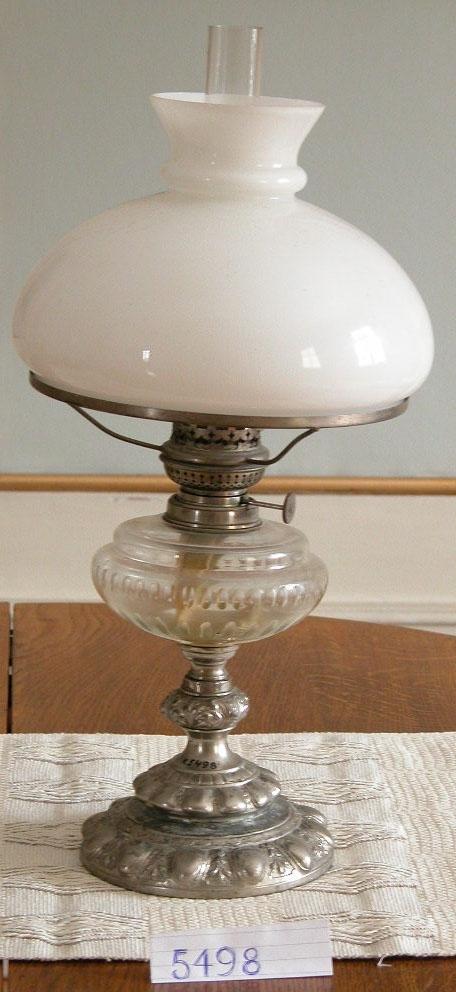 Lampa, fotogen-. Det är en bordslampa med vit kupa och fot av förnicklad mässing.