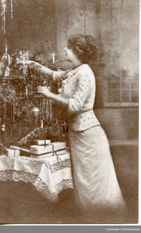 Postkort, julekort kvinne pynter juletreet.