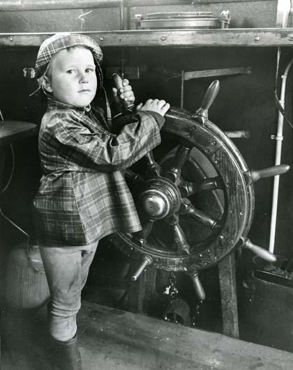 Man och barn ombord på fiskebåt i Mellanfjärden, Hälsingland. barnet bär regnkläder.