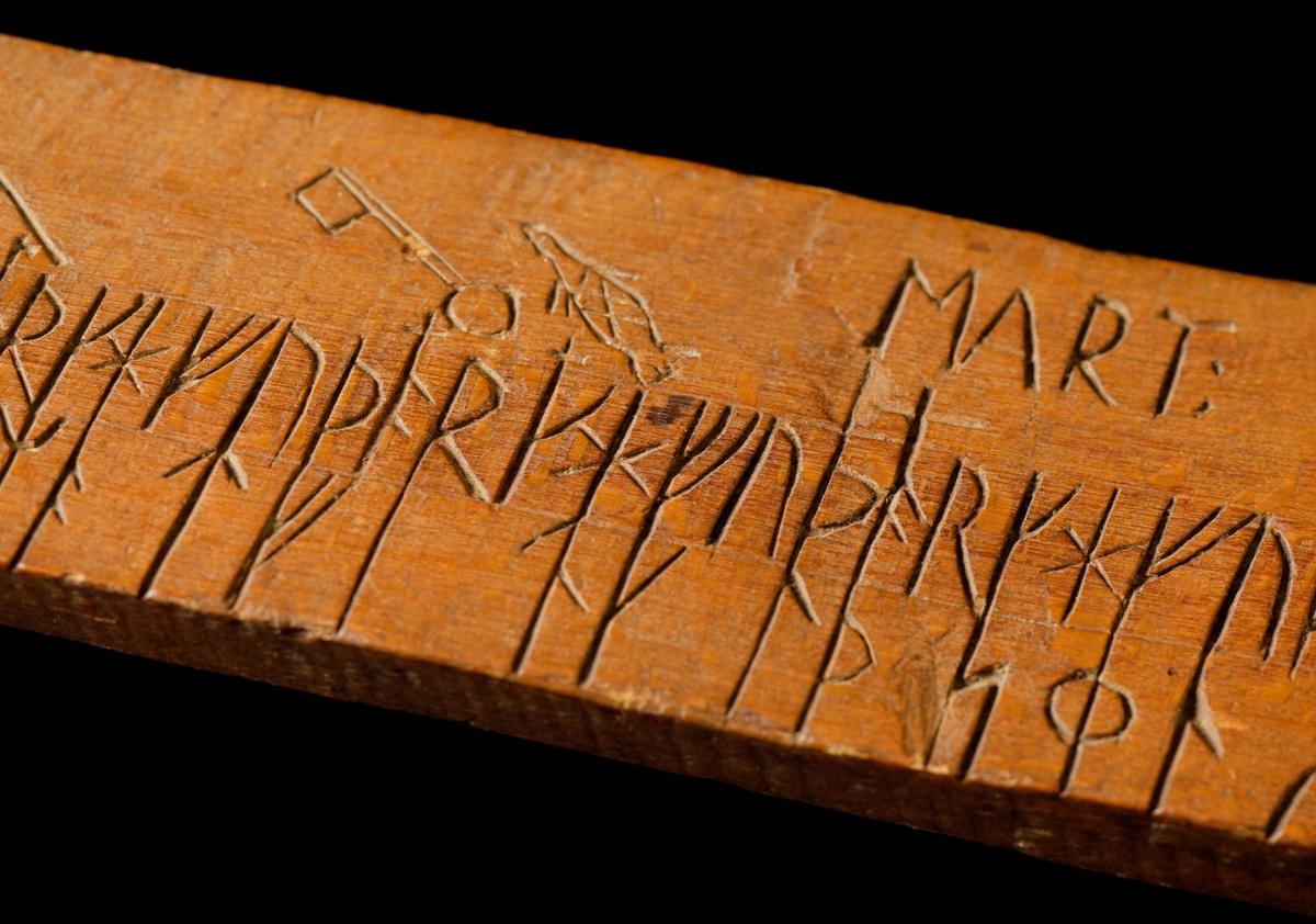 Kalenderstav i form av en runkalender. Svärdsformad och utskuren ur ett stycke bokträ. Rektangulär klinga med kalender på båda sidor. Vid spetsen med runor NILS SUNSSON samt med latinska bokstäver N:S:L:. På ena sidan vid kaveln runraden. Troligen från 1700-talets början.