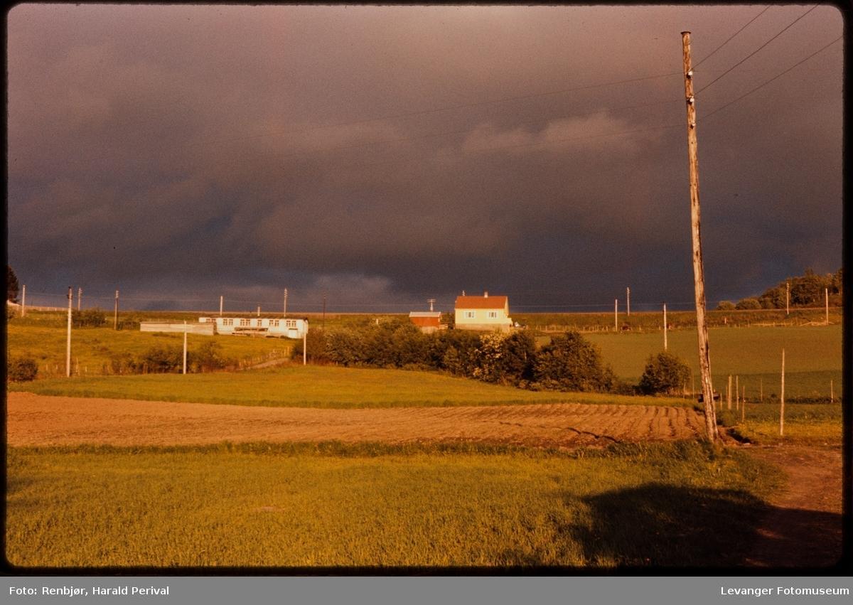 Landskap med  sol og svarte skyer, uvær brygger opp.