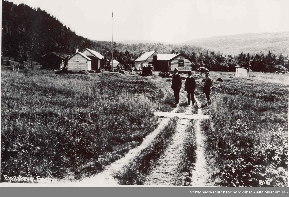 Vei som leder mot Gargia Fjellstue. Tre menn står på veien og ser mot kameraet. I bakgrunnen ser vi Fjellstua og en flaggstang.