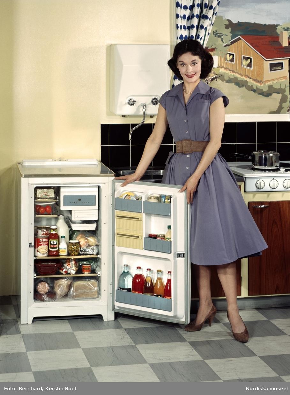 Kvinna i köksmiljö. Kylskåp med öppen dörr, fyllt med matvaror.