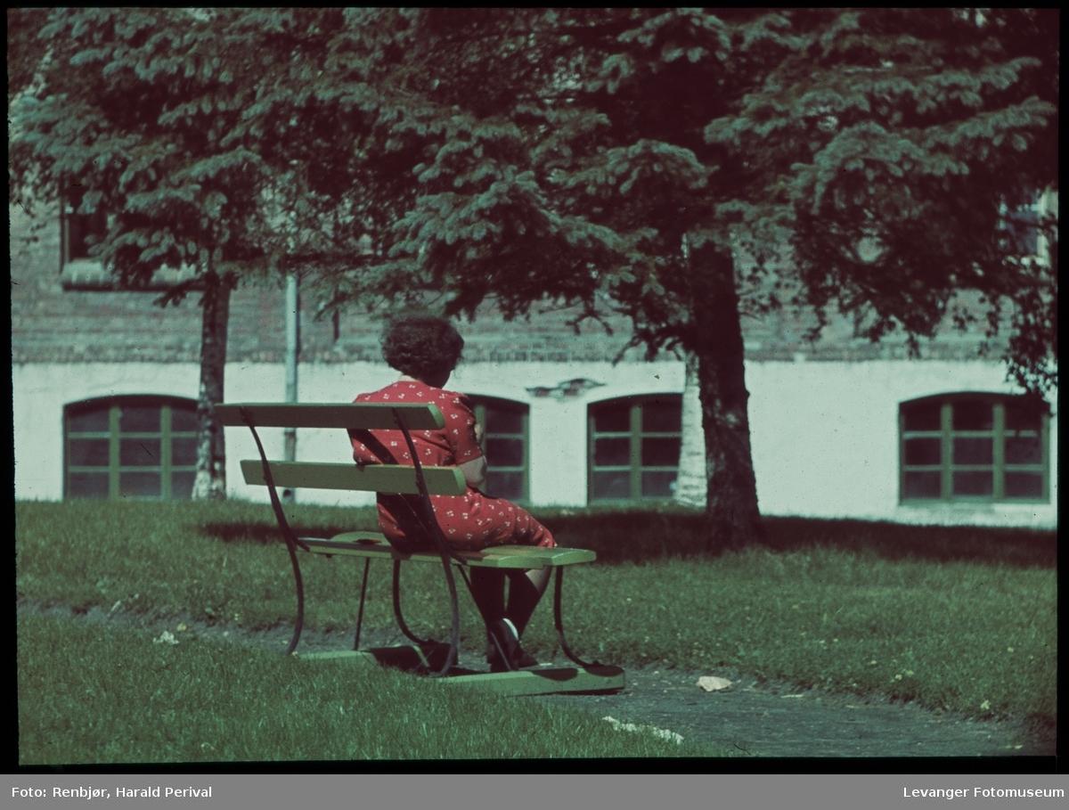 Kvinne på en benk utenfor kirka, Ullavare fabrikken i bakgrunnen.
