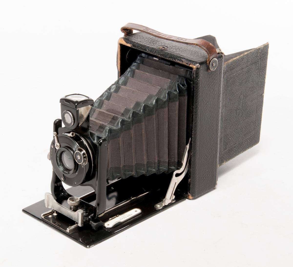 Bälgkamera Ica typ Sirene 135, tillverkningsnr G 74673. Optik Extra-Rapid-Apianat Helios, 1:8 F=13 cm nr 505968. Med sju bakstycken för bladfilm 8x12 cm och en mattskiva.