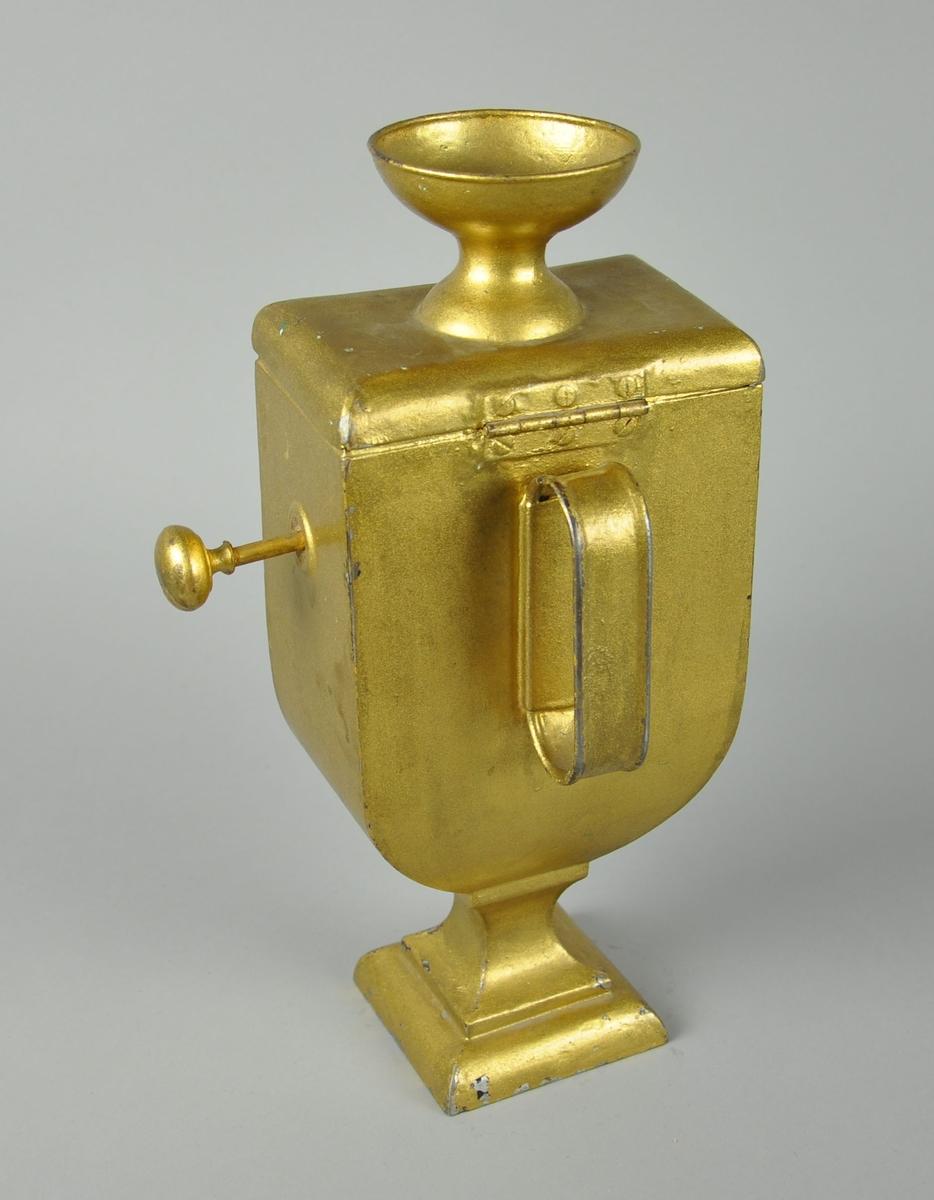 Stemmeurne av gullmalt metall. Urnen har en stående rektangulær form, der nederste parti er kurvet - denne delen går over til en sokkel. På toppen er det et hengslet lokk med skål, for å legge i balloteringskuler. På siden av urnen er det en knott som kan dras ut, for å åpne mellom skålen på lokket og resten av korpus. Urnen er malt rød på innsiden. På framsiden av urnen er det et ovalt hull. Bak urnen er det et håndtak.