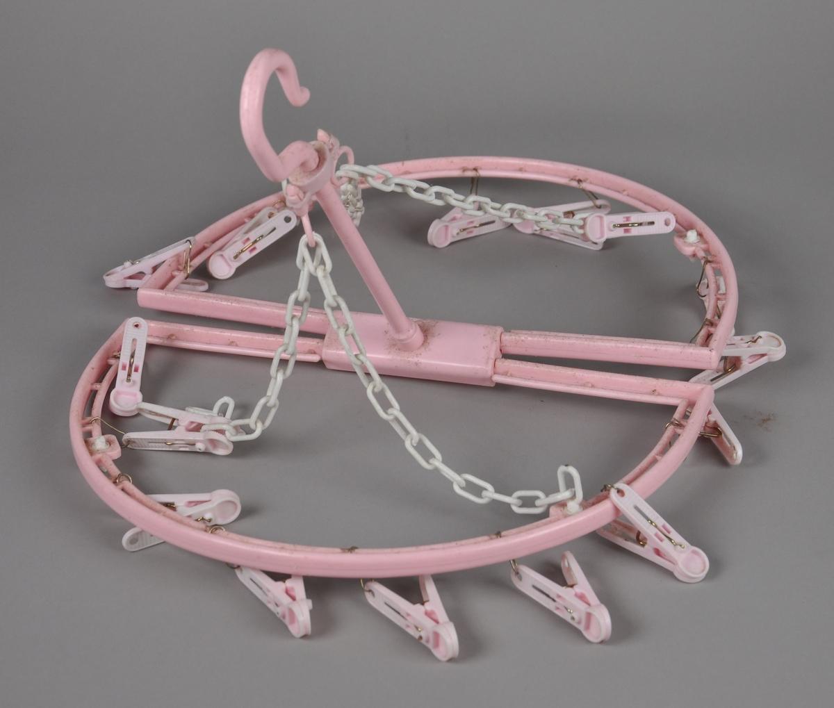 Utbrettbar kleshenger til småvask. Er laget av rosa og hvit plast, og har en oval form når den er brettet ut. Har en krok på midten for oppheng.