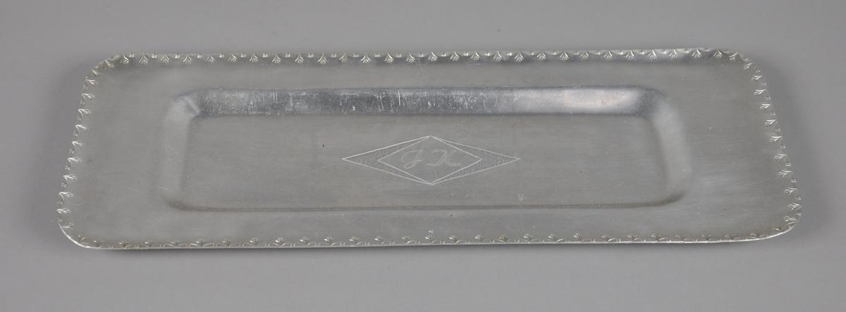 Fat av metall med innrisset dekor ved kanten, med motiv av blomster. Fatet er rektangulært og med innskrift på midten. Fatet er opphøyd ved kanten.