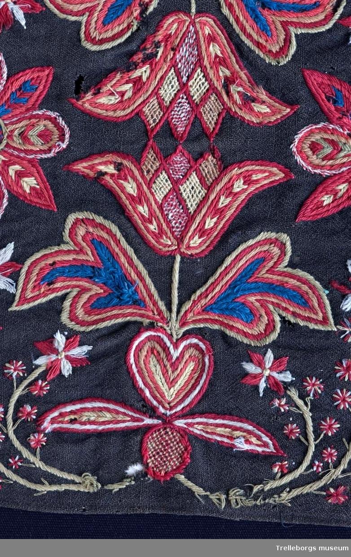 Botten är svartbrun tuskaft i ullgarn.  Ringkrans med 4 blommor. Hela mönstret är spegelvänt utmed en längsgående axel (frånsett 2 tulpanfigurer och märkningen ALD HMDG utmed den övre långsidan och ANNO 1838 utmed den nedre långsidan.  Broderiet består av gängse fantasiblommor och tulpaner, omgivna av bladslingor. Färgerna är vitt, blekgult, blekgrönt, blått, bronsgult mm