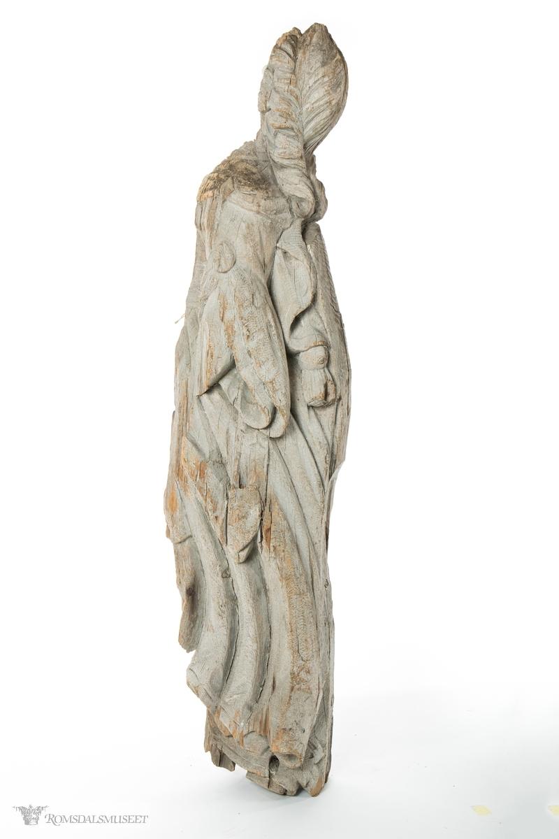 Kvinnefigur i tre som er delt i to på langs slik at bare bakhodet og ryggen av figuren er inntakt. Kvinnefiguren har en lang kjole/kappe med sjal, hår flettet i en bue som er satt opp rundt hodet og som ender i en flette nedover ryggen som stikker ut fra kappen eller sjalet.