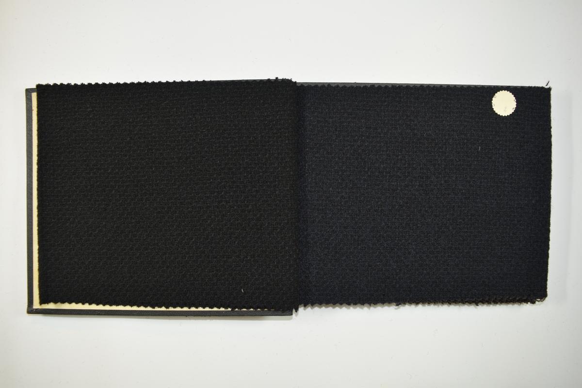 Prøvebok med 6 prøver. Relativt tykke ensfargede stoff. Stoffene ligger brettet dobbelt slik at vranga dekkes. Stoffene er merket med en rund papirlapp, festet til stoffet med metallstift, hvor nummer er påført for hånd.  Innskriftene på innsiden av forsideomslaget beviser hvilke kvalitetsnummer stoffene har.   Stoff nr.: 98/1, 98/2, 98/3, 98B/25, 98B/26, 98B/27.