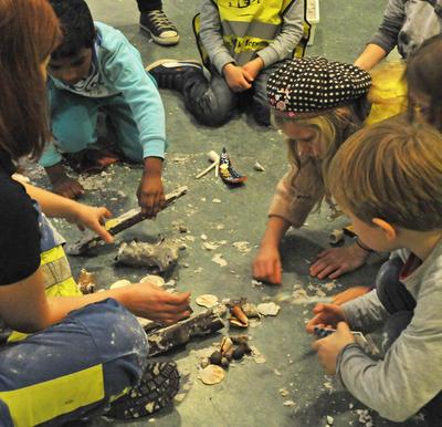 Barn sitter i sirkel, leker arkeologer, graver ut funn fra sandkasser.. Foto/Photo