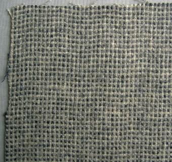 Vävprov, gråblå-melerat kostymtyg i ull vävt i panamabindning med färgeffekt. Tyget är valkat.  Varp och inslag i grått och blått ullgarn.