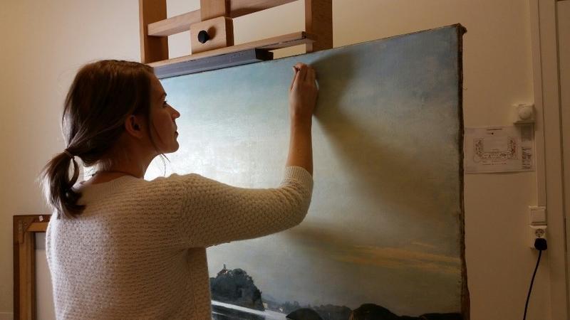 Gjenstands- og malerikonservator Kristine Draugedalen renser et landskapsmaleri. Foto: MiA.