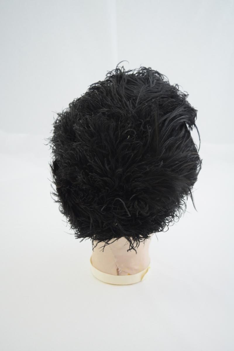 Sort damehatt. Pullen helt dekket av sorte strutsefjær, kant av sort silkeatlask. Hvitt silkefor med merker etter hattenåler.