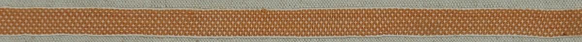 Band 155 x 1,2 cm. Bomull, mönstrat i orange och vitt.  Katalogiserad av Karin Nordenfelt, Elisabet Stavenow, Marie-Louise Wulfcrona-Dagel.