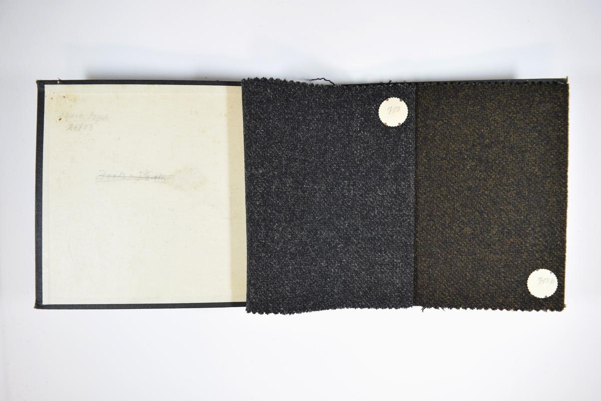 Prøvebok med 2 stoffprøver. Middels tykke stoff med diskret prikker. Tofargede stoff. Stoffene ligger brettet dobbelt slik at vranga skjules. Stoffene er merket med en rund papirlapp, festet til stoffet med metallstifter, hvor nummer er påført for hånd.   Stoff nr.: 700, 700B.