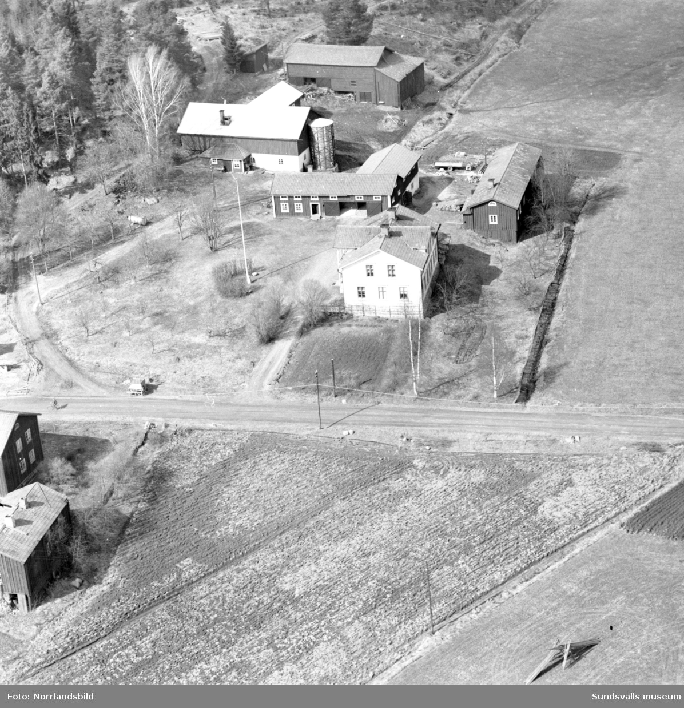 Flygfoto över en oidentifierad gård, troligen någonstans i Selånger. På bild två har helikoptern landat på en lägda och människor har samlats runt den.