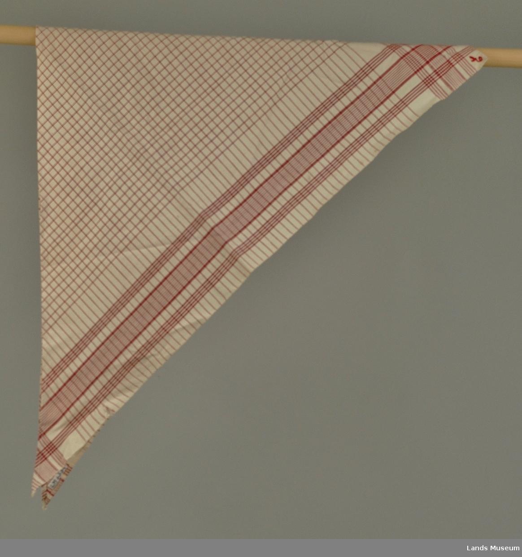 Tøyet er tett, toskaftsvevd med ubleket bomull som bunnfarge. Midtpartiet er rutet opp med smale røde striper i 3/4 cm avstand som danner ruter. 12 cm fra jaren stanser rutingen, men stripenen fortsetter og midt på denne kanten, går en 2,5 cm bred bord, smalstripete på midten, noe bredere ytterst. På hver side løper 4 middels brede striper. Disse bordstripene krysser til ruter i hjørnet. Tørkleet er klippet til diagonalt av et tøy ca. 80 x 80 cm. Diagonallinjen og ene rette siden har maskinfald.