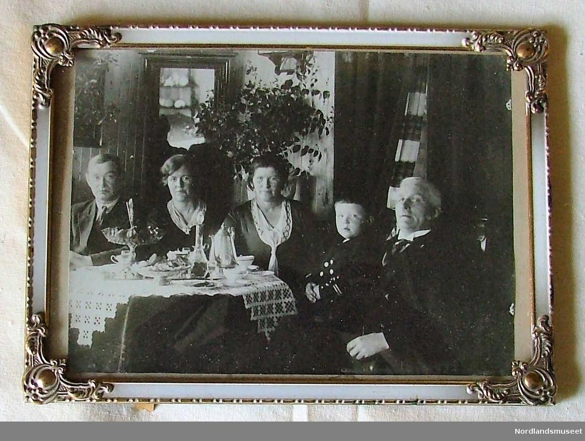 Innrammet sort/hvitt fotografi i metallramme og glass. To kvinner, to menn og en ca. 3-4 år gammel gutt ved et lite, men vakkert pyntet kaffebord.