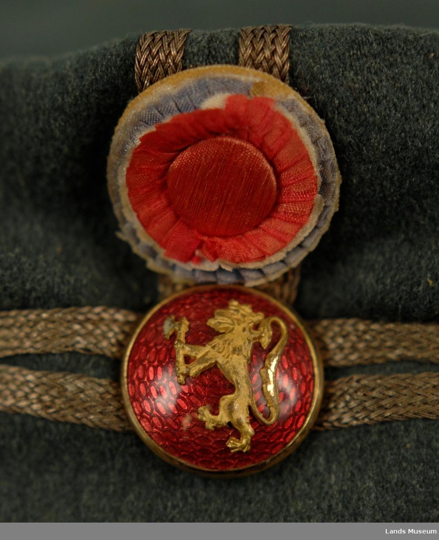 Grøn militærlue med svart skygge. Lua er foret med rosa ullstoff. 2 svarte knapper. Sølvfargt 54 mm bånd rundt lua og opp til pullen. Foran en nasjonalfarget knapp av silkebånd og en forgylt knapp på rød bunn med norsk løve.