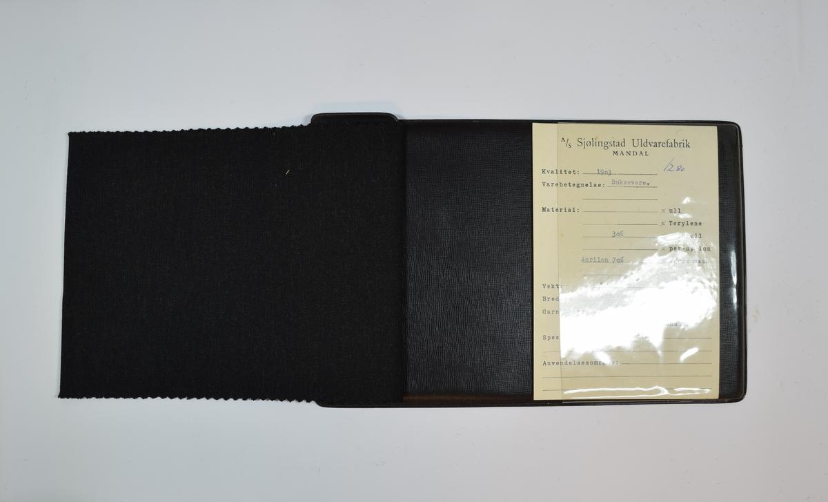 Prøvehefte med én stoffprøve. Relativt tynt, men tett, melert stoff. Kyperbinding/diagonalvevd. Stoffet ligger brettet dobbelt i heftet slik at vranga dekkes. Stoffet er merket med en firkantet papirlapp klistret til stoffet, hvor nummer er påført for hånd i et trykket skjema. Heftet har stiv bakplate dekket av plast, og samme type plate på forsiden som dekker ca. 5 cm der heftet er stiftet. To messingskruer holder heftet sammen.   Stoff nr.: 1935/1, rettet til 1903/1 med overskrevet penn.