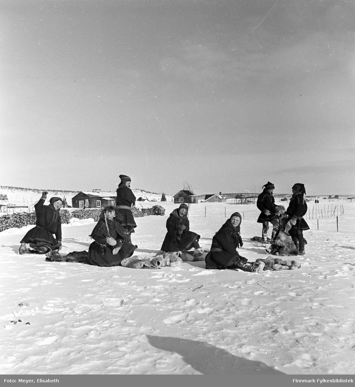 Utenfor Kautokeino skoleinternat. Skolebarna banker dorkene i snøen.